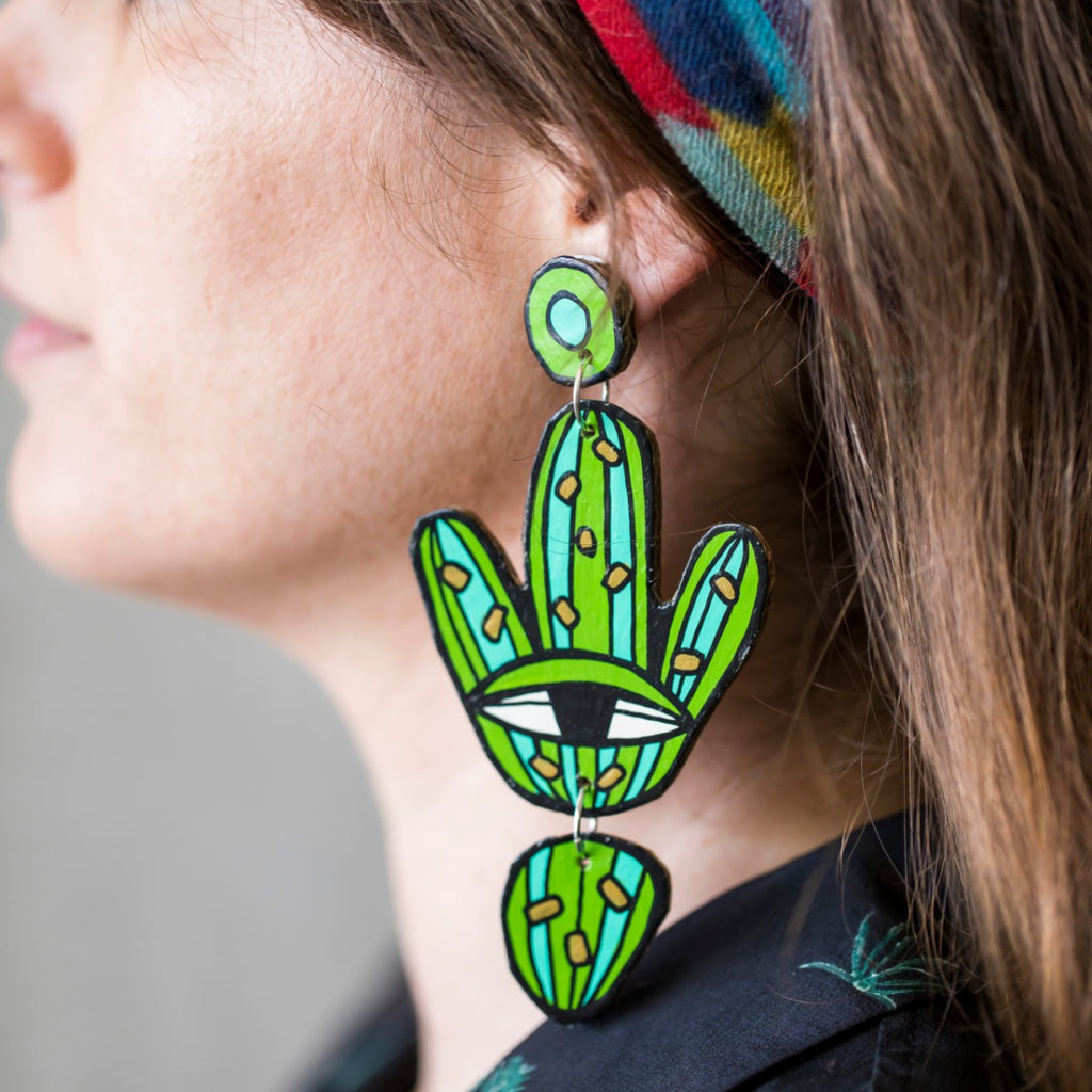 A beautiful woman wears a pair of Jeff McCann drop earrings. Featuring an eye and cactus like shapes and colours in green, teal white and brown.