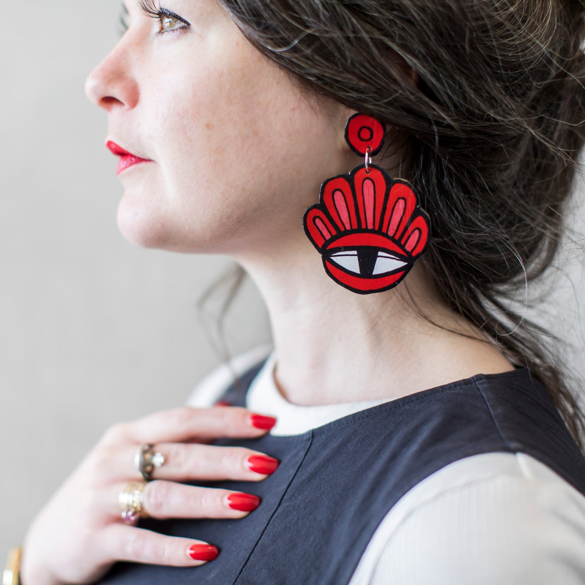 A beautiful woman wears a pair of Jeff McCann drop earrings. Featuring an eye and bloom like petals in Red, Pink, white and black
