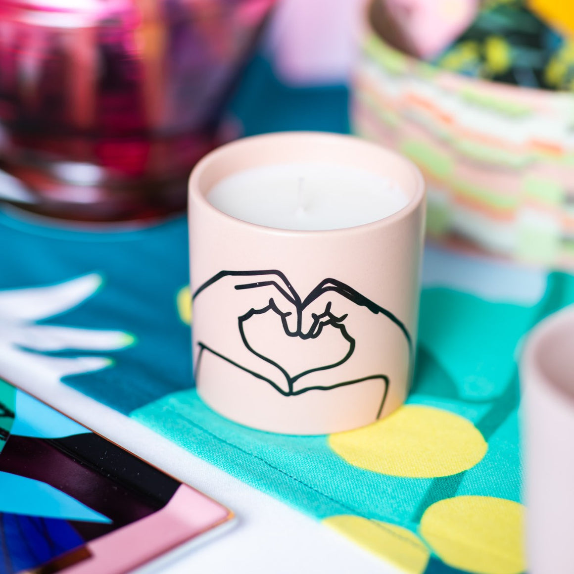 Image featuring a pastel pink ceramic candle which includes in the middle a graphic illustration two hands which have been shaped to look like a love heart. Surrounded by other homewares