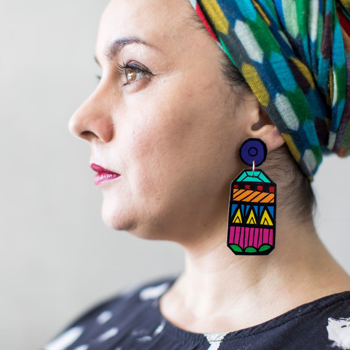 A beautiful woman wears a pair of Jeff McCann drop earrings. Featuring an an abstract gemstone inspired pattern in green, pink, yellow ,blue, orange, red and turquoise