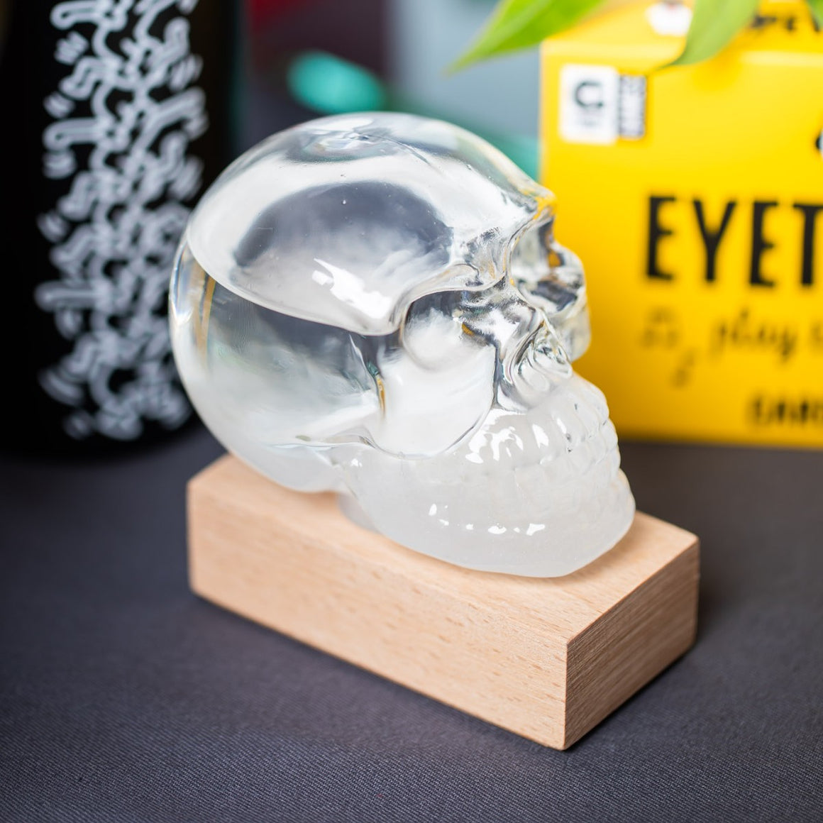 A glass skull containing liquid sits atop a beech wood base,