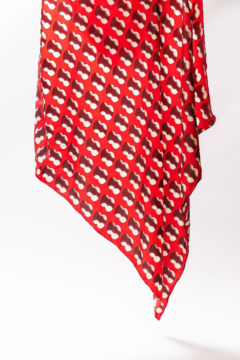 A large silk scarf featuring artwork Double Negative by Cornelia Parker in Red and white is shown suspended with one corner pointing towards the ground
