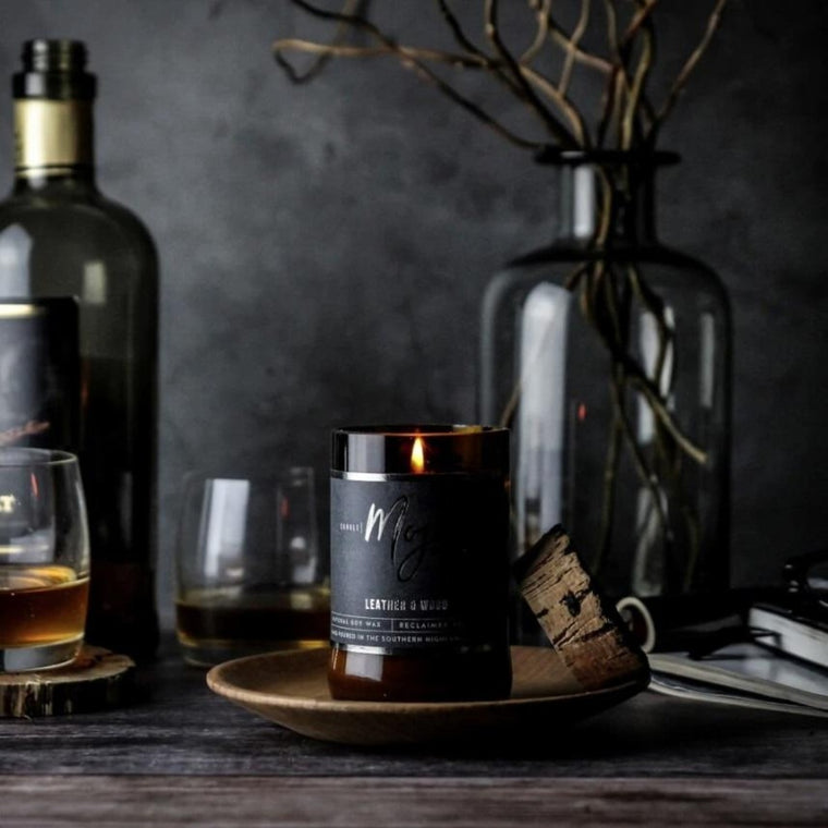 Candle featured in a recycled brown beer bottle centered around a dark background including clear glass bottles with branches in it, glasses of scotch, books and bottle of scotch
