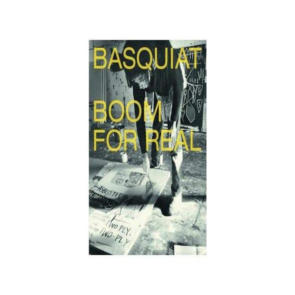 Book cover featuring a black and white photograph with the artist Basquiat painting a work in his studio