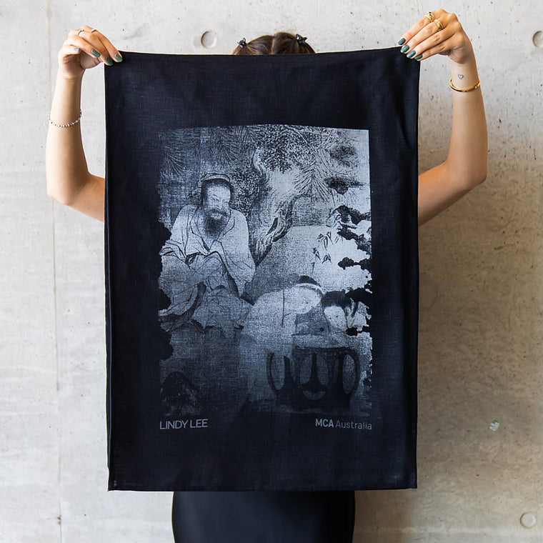 A woman holds up a black teatowel. Printed in white is the Lindy Lee artwork True Chien depicting a man with two children in a natural setting.