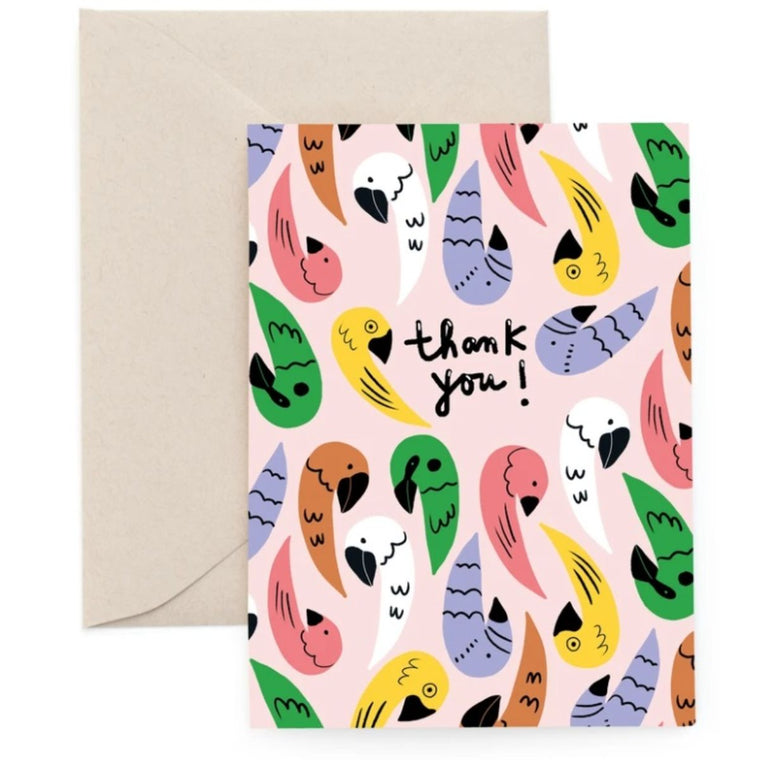 Greeting Card in a pastel peach colour featuring a graphic illustration of parrots in multiple colours including the words Thank You!