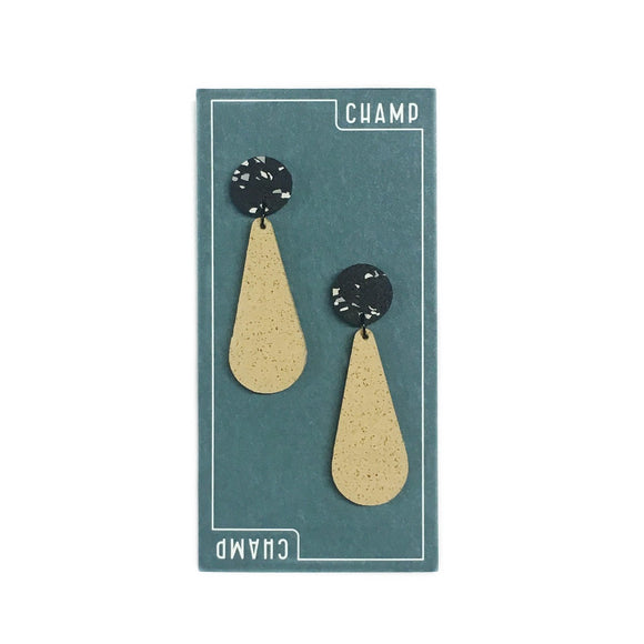 Navy blue card featuring a white lined border with the word Champ on it which includes two exclamation drop earrings in a sand yellow and black and white fleck colours