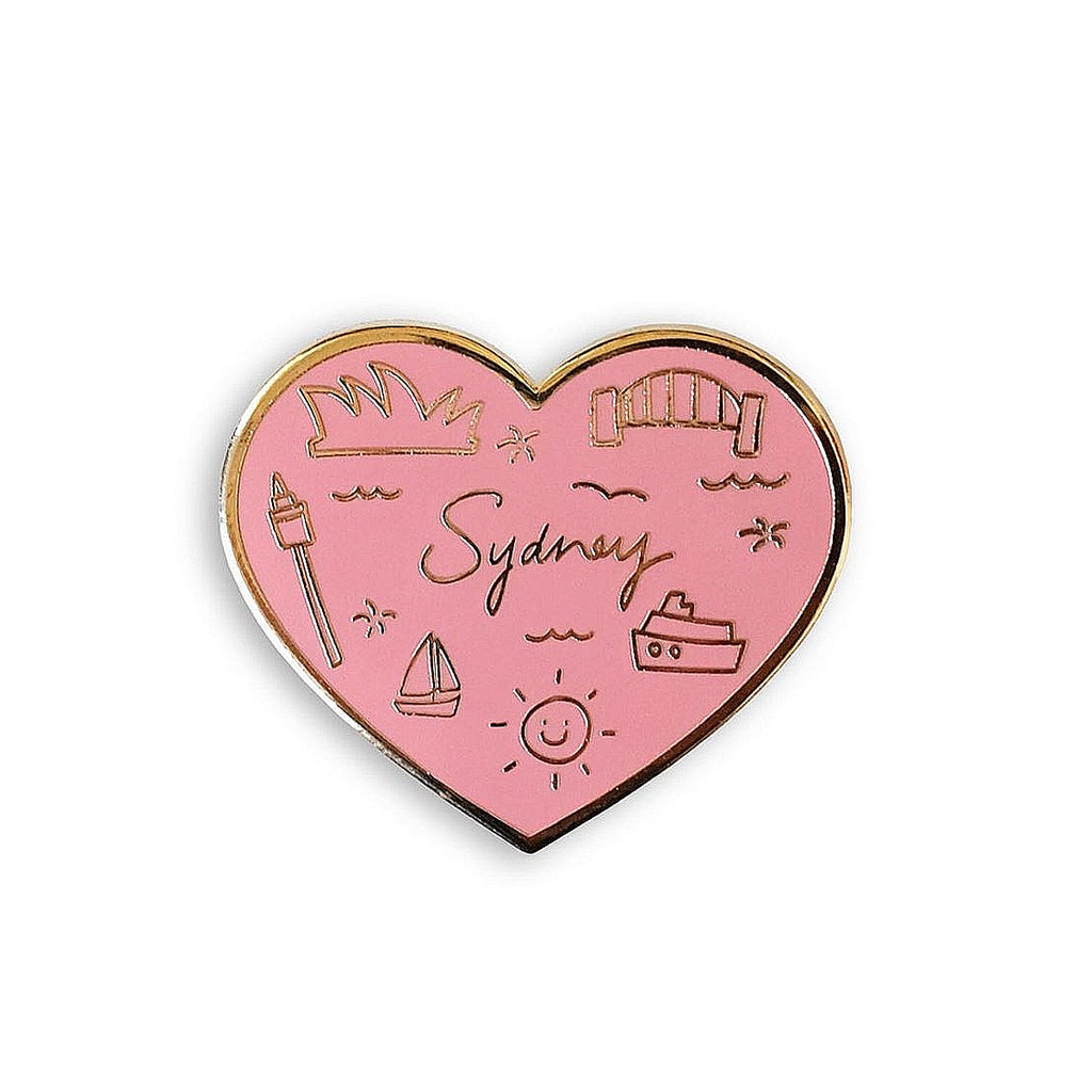 A love heart shaped enamel and gold pin. The word Sydney and sydney icons are rendered in gold, and then the pin is filled with pink enamel.