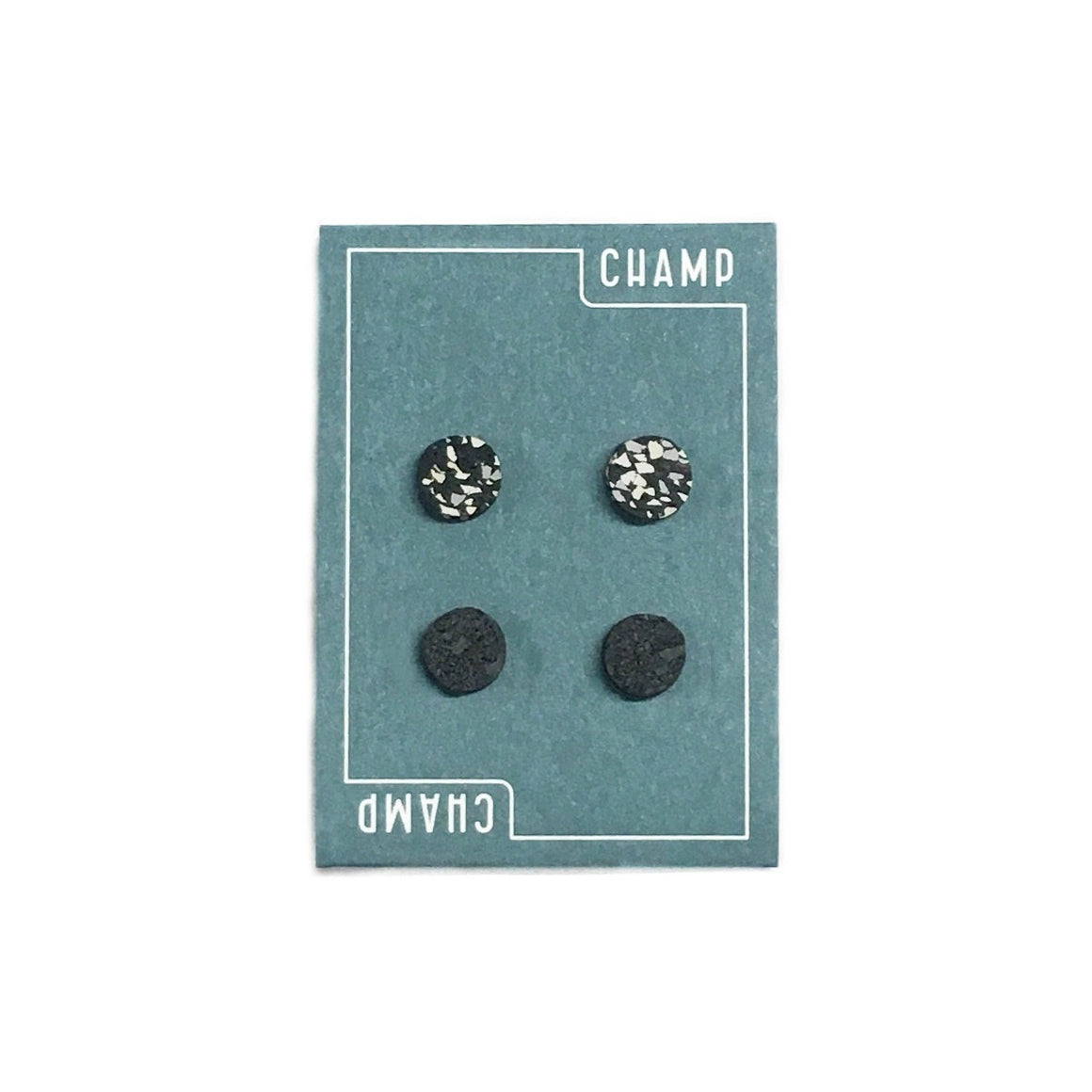 Navy blue card featuring a white lined border with the word Champ on it which includes four studs two in black and then the other two in a black and white speckle