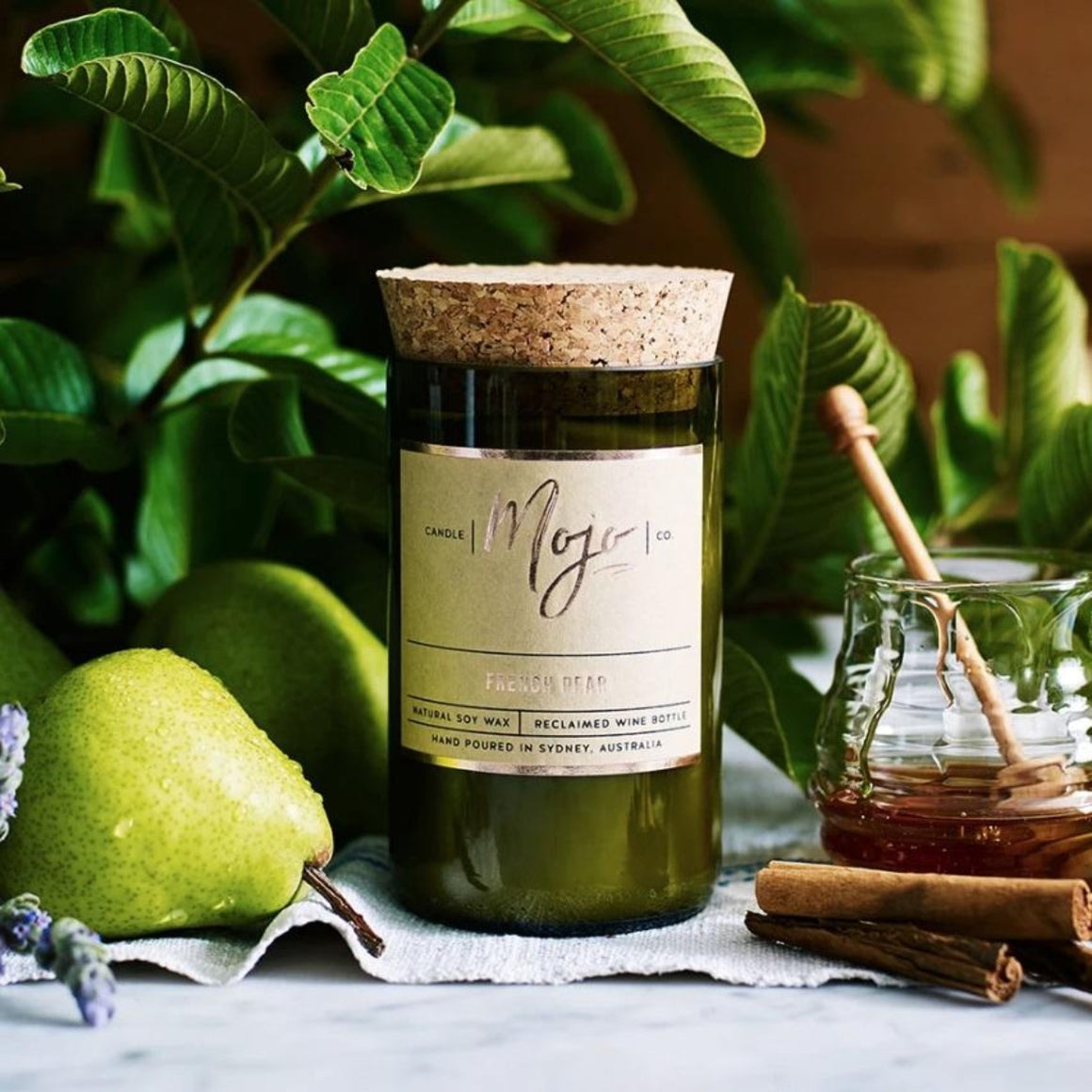 Candle featured in a recycled green wine bottle centered around a leaf filled background including pears, lavender, honey and cinnamon sticks