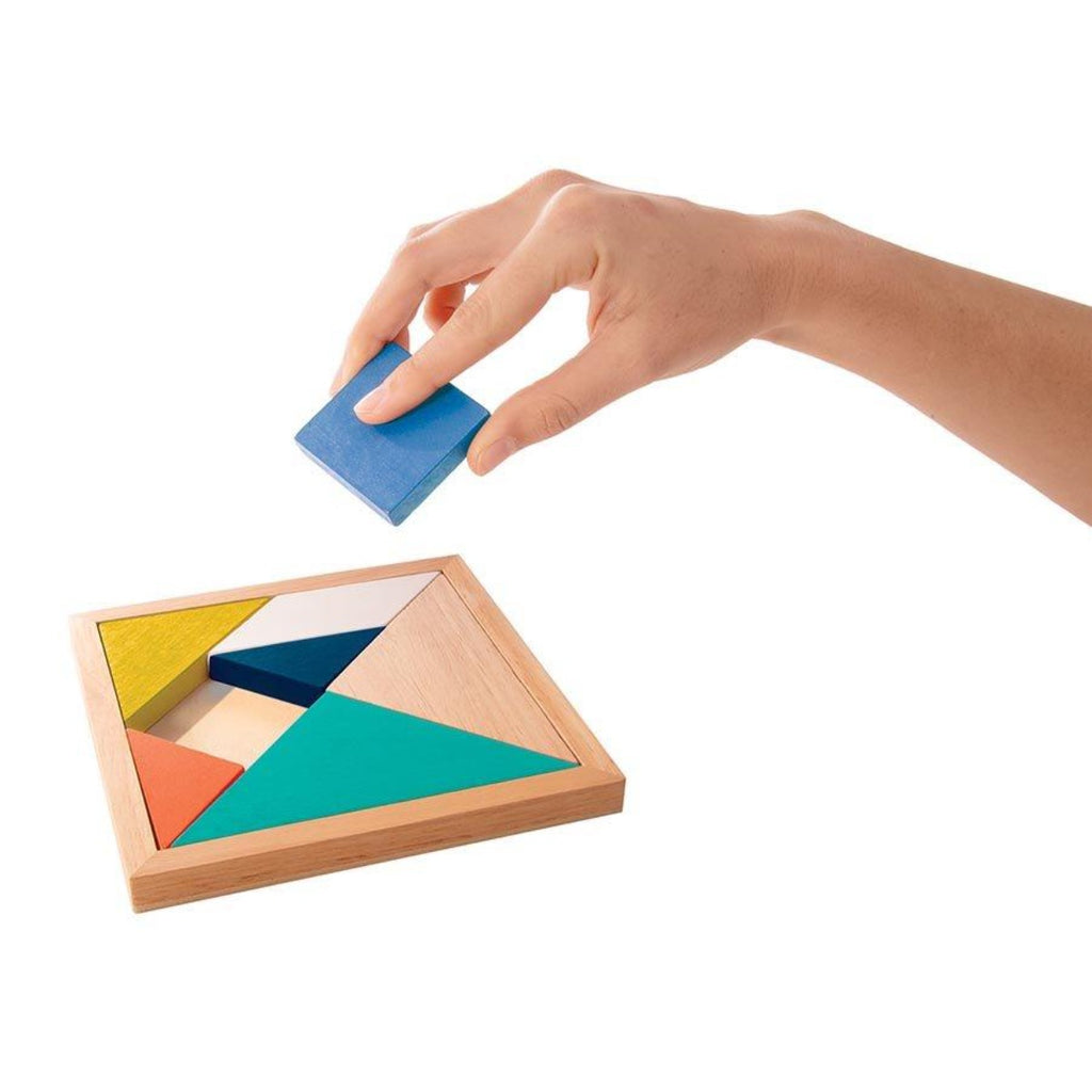 Image featuring a hand playing the classic tangrams game, they are holding a square blue piece above the nearly completed game