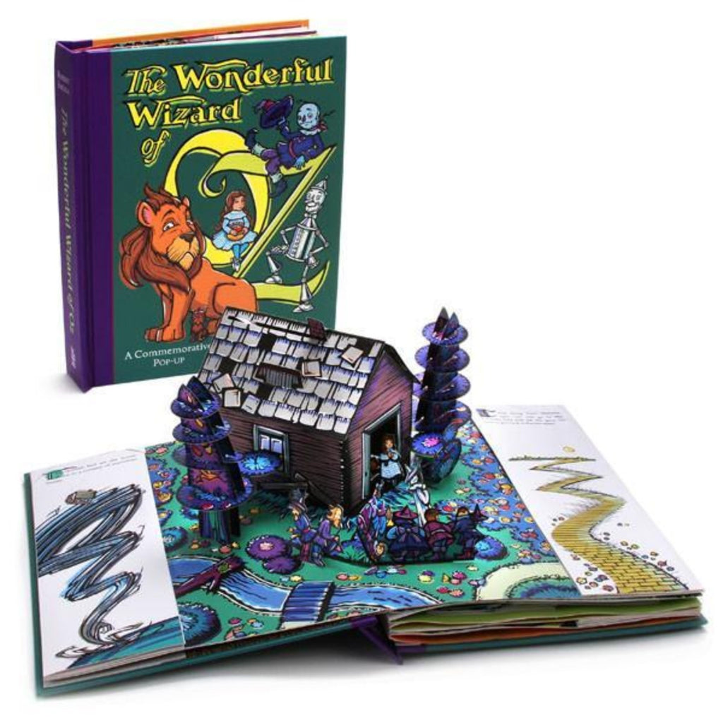 Photograph of the book cover with the book open in front to display a page of the pop up featuring a house, Dorothy and trees