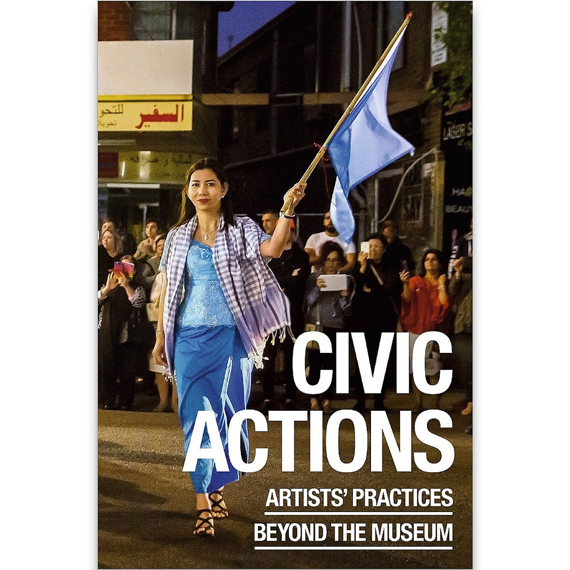 "A book cover entitled 'Civic Actions Artists' Practices Beyond the Museum"" in white text overlaid on  photograph. The photograph depict a woman in a blue dress and purple checked staff waving a blue flag in front of a crowd of onlokers."