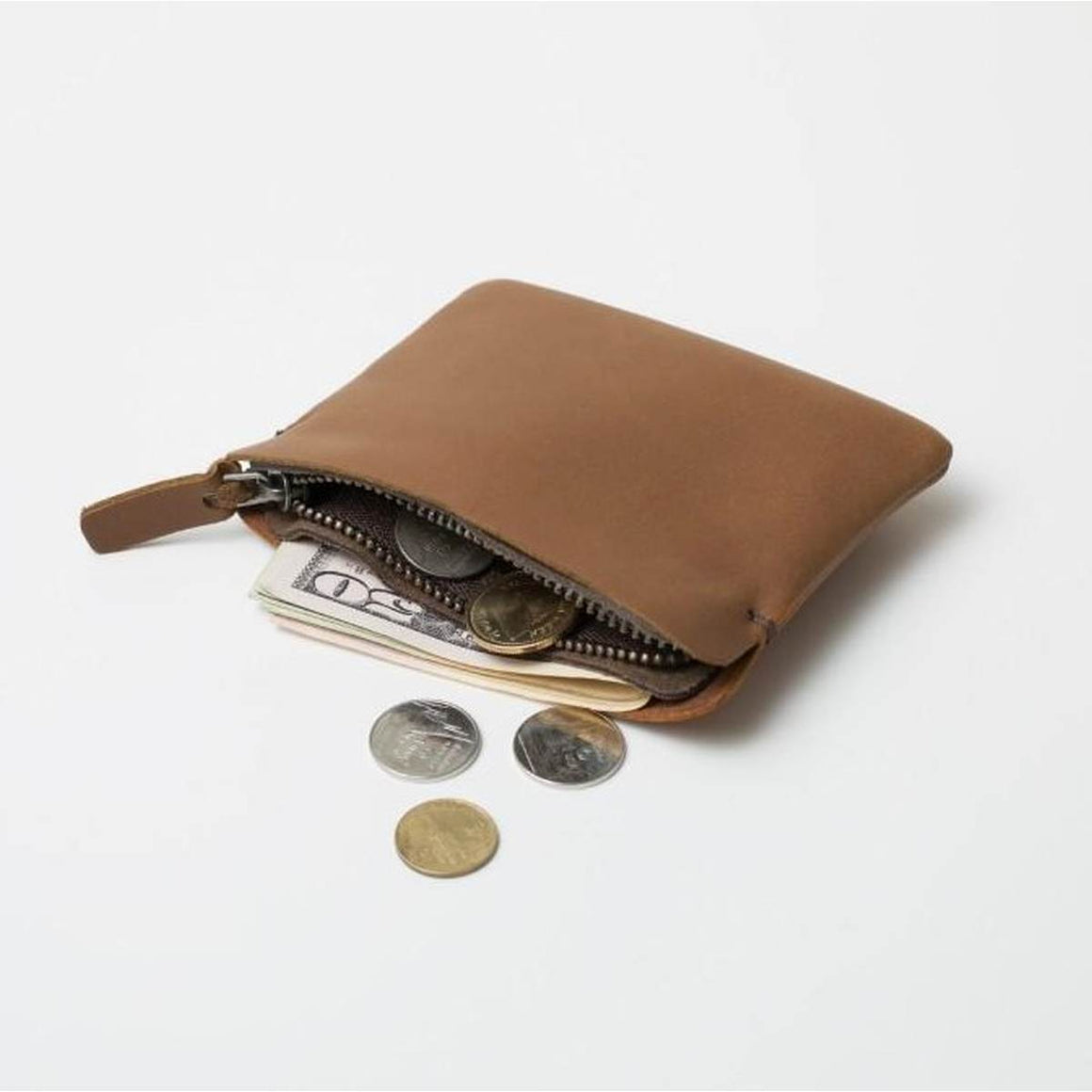 A small tan leather wallet featuring pockets for bank notes and a zipped pocket for coins. shown open with money spilling out