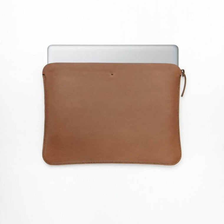 A tan brown leather laptop case wit ha zip closure. Shown holding a laptop.