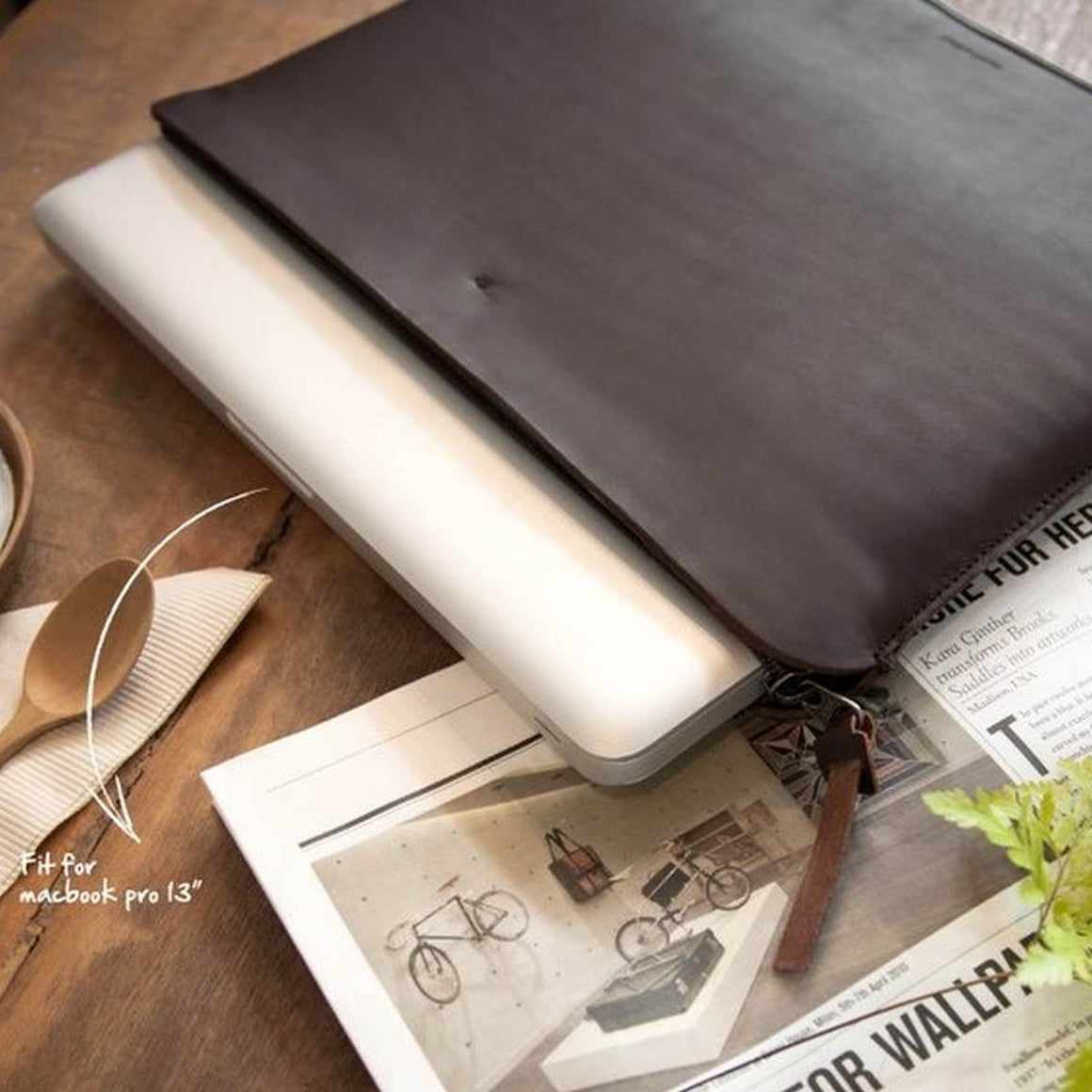 A dark brown leather laptop case with a zip closure. Shown holding a laptop.