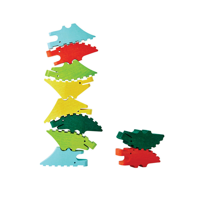A toy Set of wooden stacking blocks, each in the shape of a stylised crocodile. Painted in tones of green red and blue. Shown stacked on top of eachother.