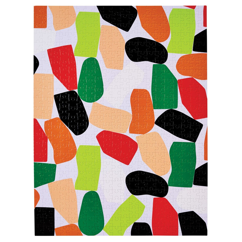 A 500 piece puzzle featuring an abstract design by Dusen Dusen. Geometric and abstract shapes in red, orange, cream, light green and dark green on a pastel purple base.
