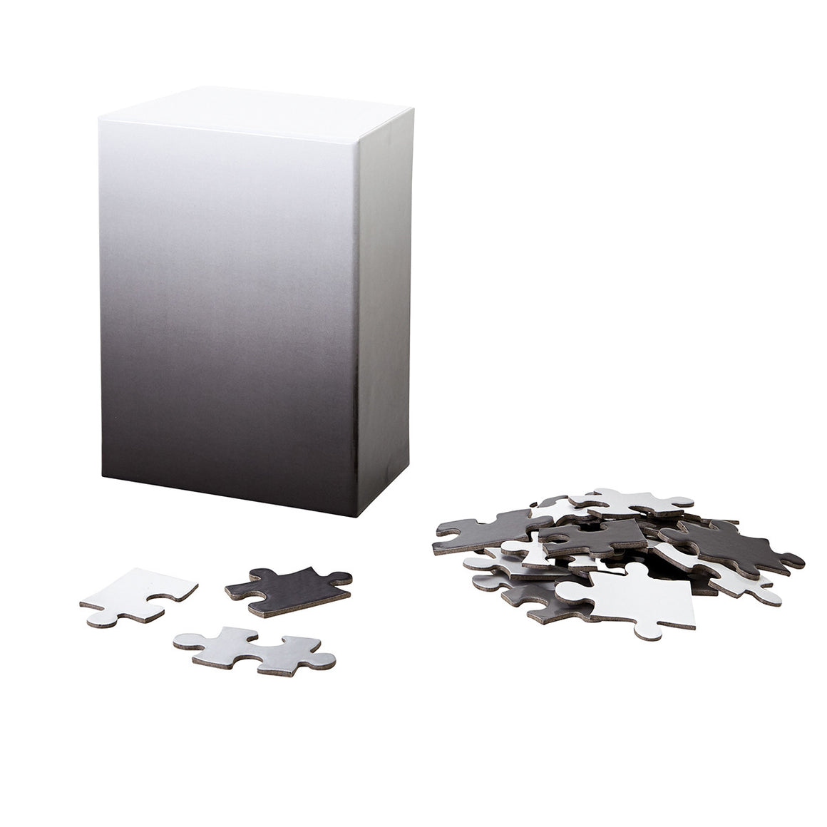 A puzzle in a tonal gradient from black to grey to white. The image shows the puzzle box next to a pile of assorted puzzle pieces.