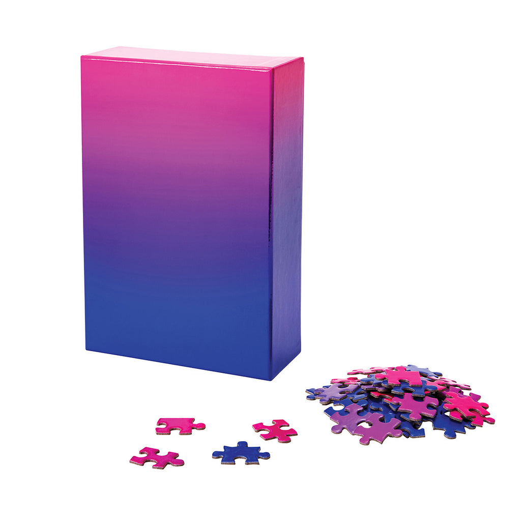 A puzzle in a tonal gradient from neon pink to deep electric blue. The image shows the puzzle box next to a pile of assorted puzzle pieces.