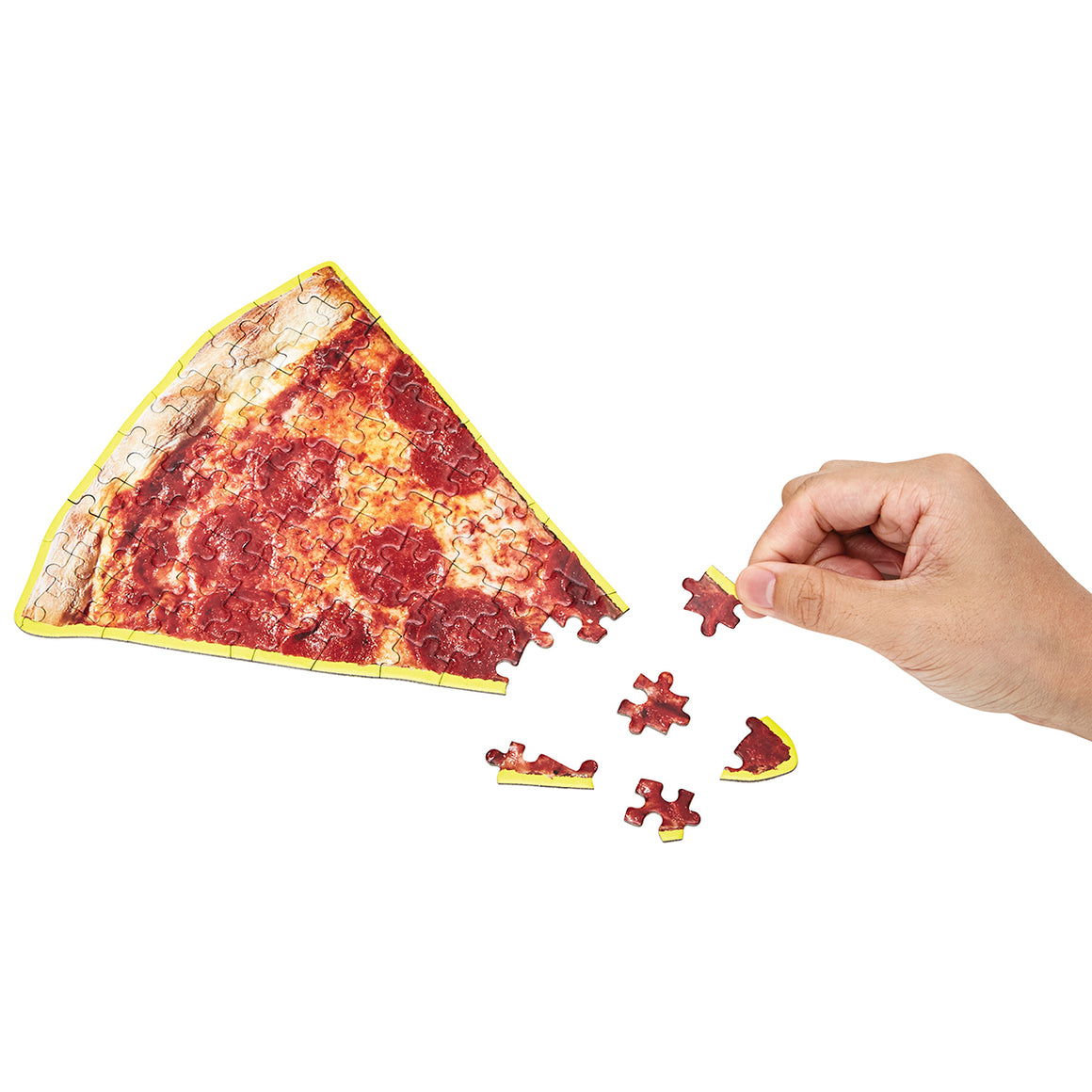 A cute puzzle in the shape and print of slice of Pepperoni pizza. Shown almost complete, with a hand placing pieces.