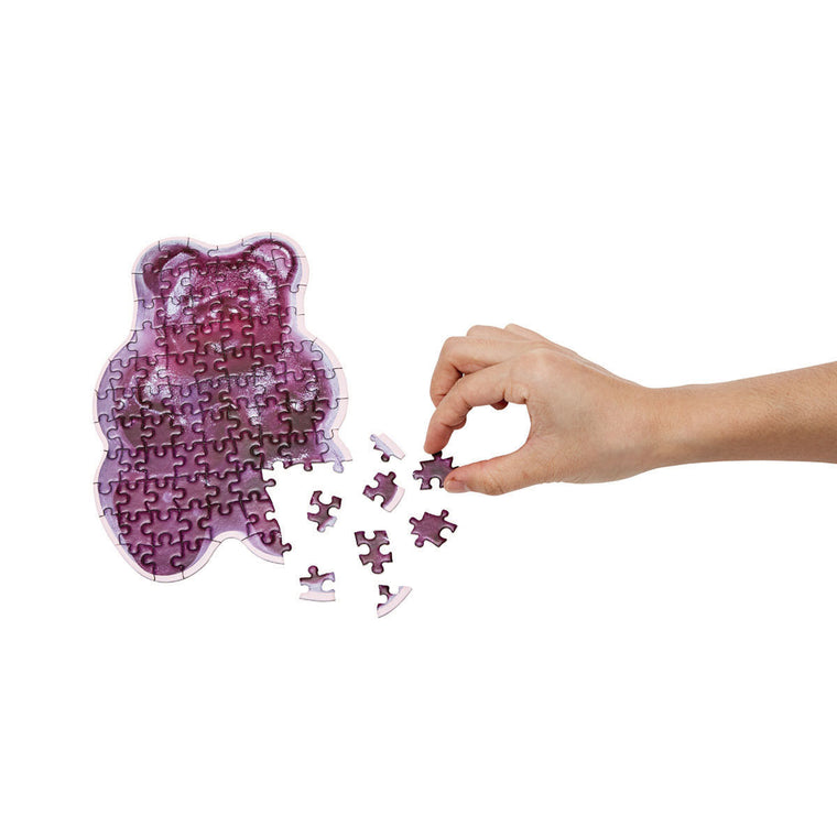 A cute puzzle in the shape and print of a Gummy Bear Candy. Shown almost complete, with a hand placing pieces.