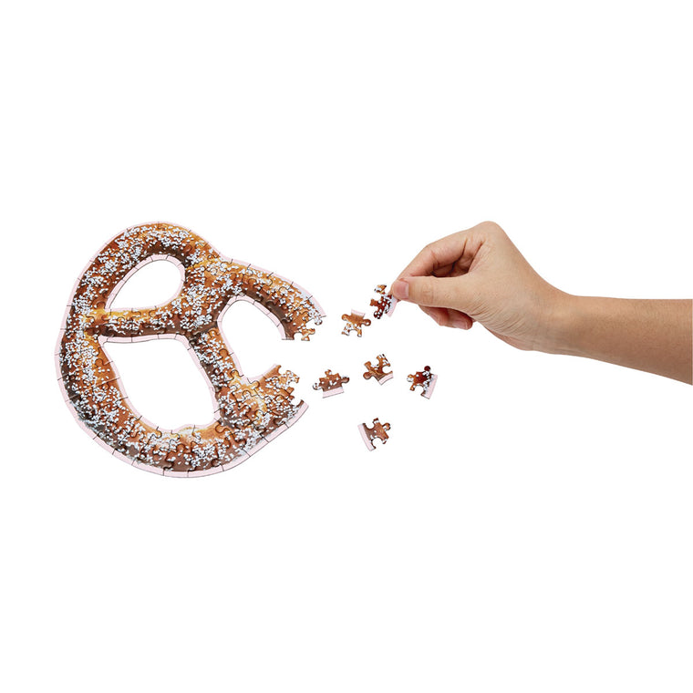 A cute puzzle in the shape and print of a large American style soft pretzel. Shown almost complete, with a hand placing pieces.
