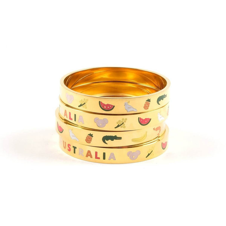 "A stack of four gold bangles featuring australian icons and the word ""AUSTRALIA"" inset in enamel"