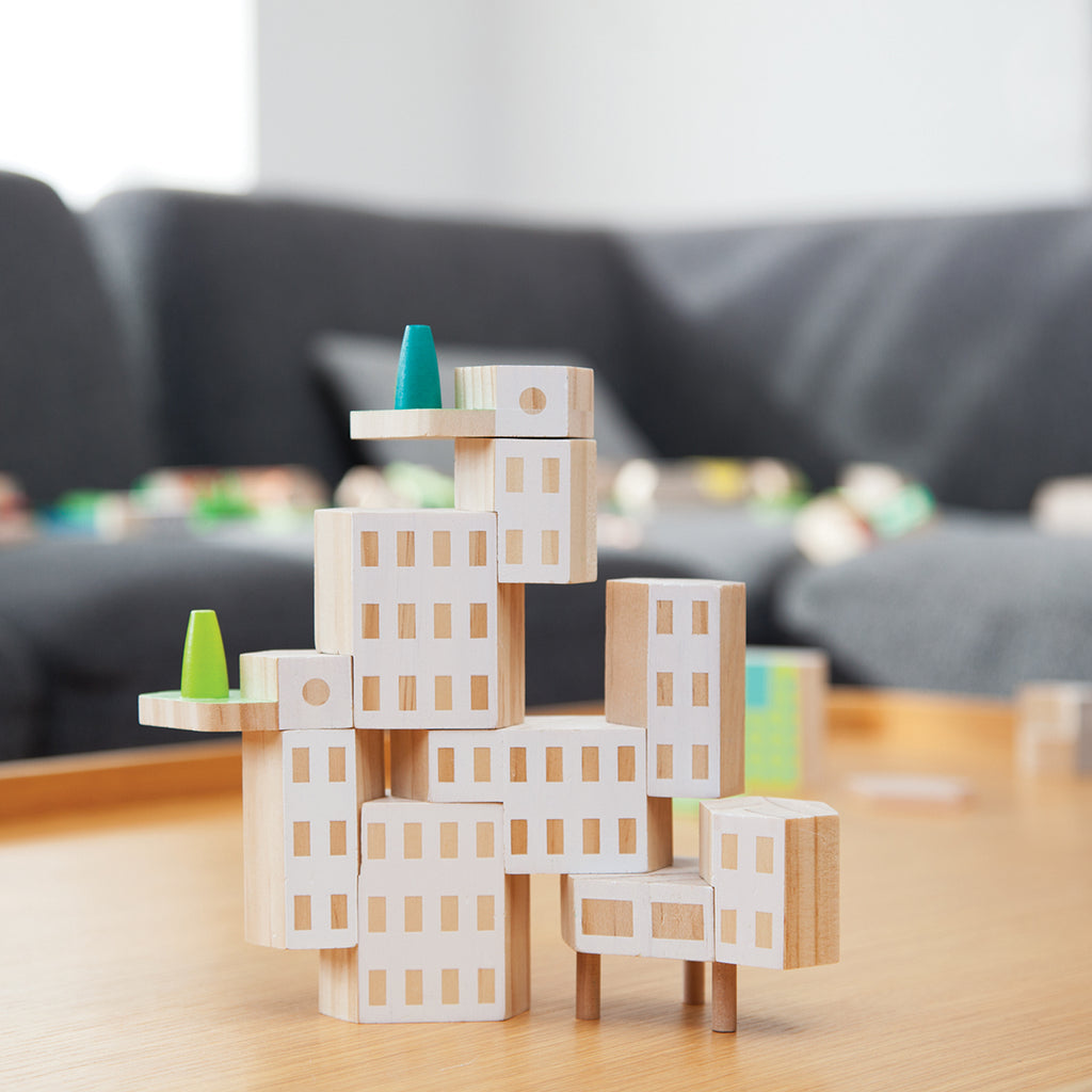 A garden city set of building blocks made of painted wood in featuring towers, a pavilion and garden terraces, made of painted wood.