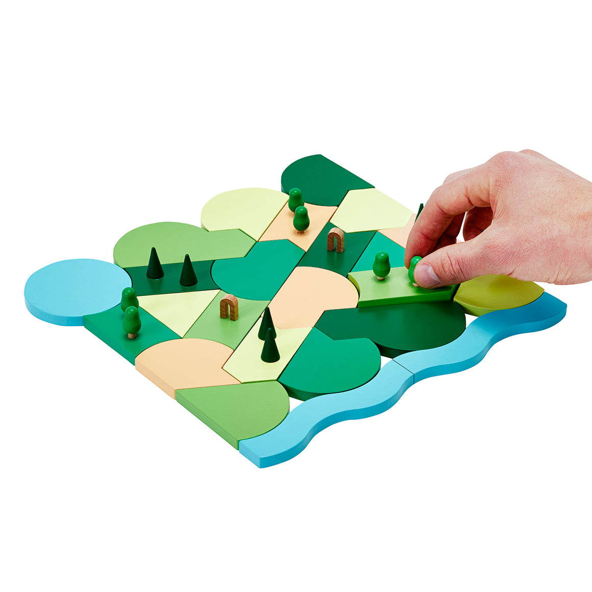 A parkland set of building blocks made of painted wood in greens, blues and sand colours as well as small Trees and arches. A hand is shown positioning the tree.