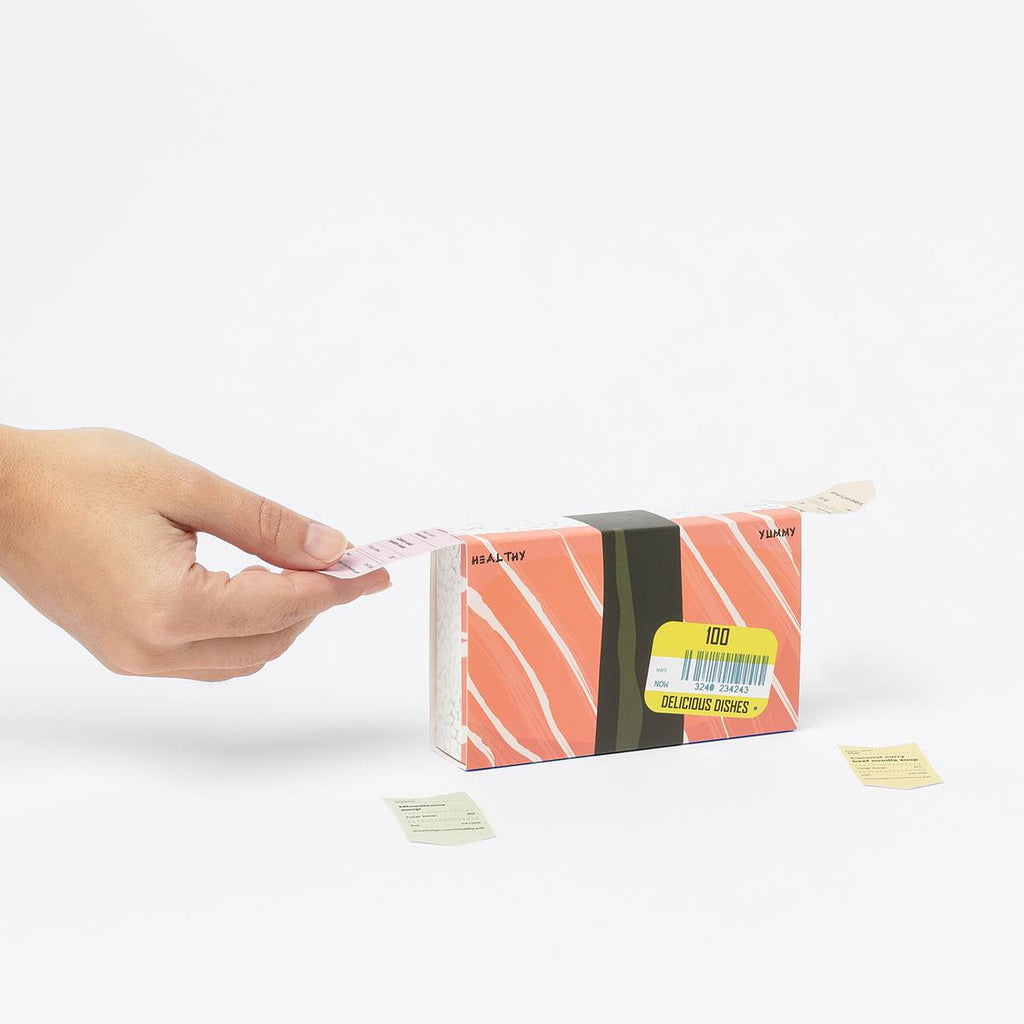 A box that dispenses issues tickets from two sides and has a salmon print featured on the box.  On one side tickets are dispensed labelled healthy, on the other side tickets are dispensed that are labelled yummy. A hand is selecting a ticket from the box.