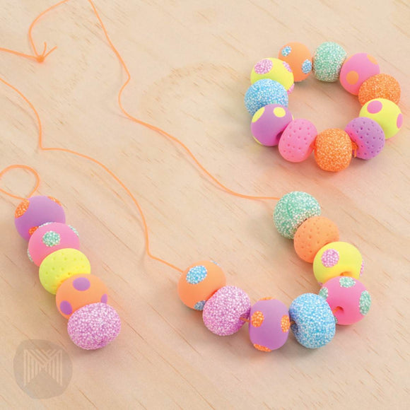 "An Air Clay jewellery kit in 'lollipop colours' of bright orange, pink, yellow, purple, green and blue. The box shows completed multicolour beaded bracelets and necklace and text states ""Makes 24 Beads"""