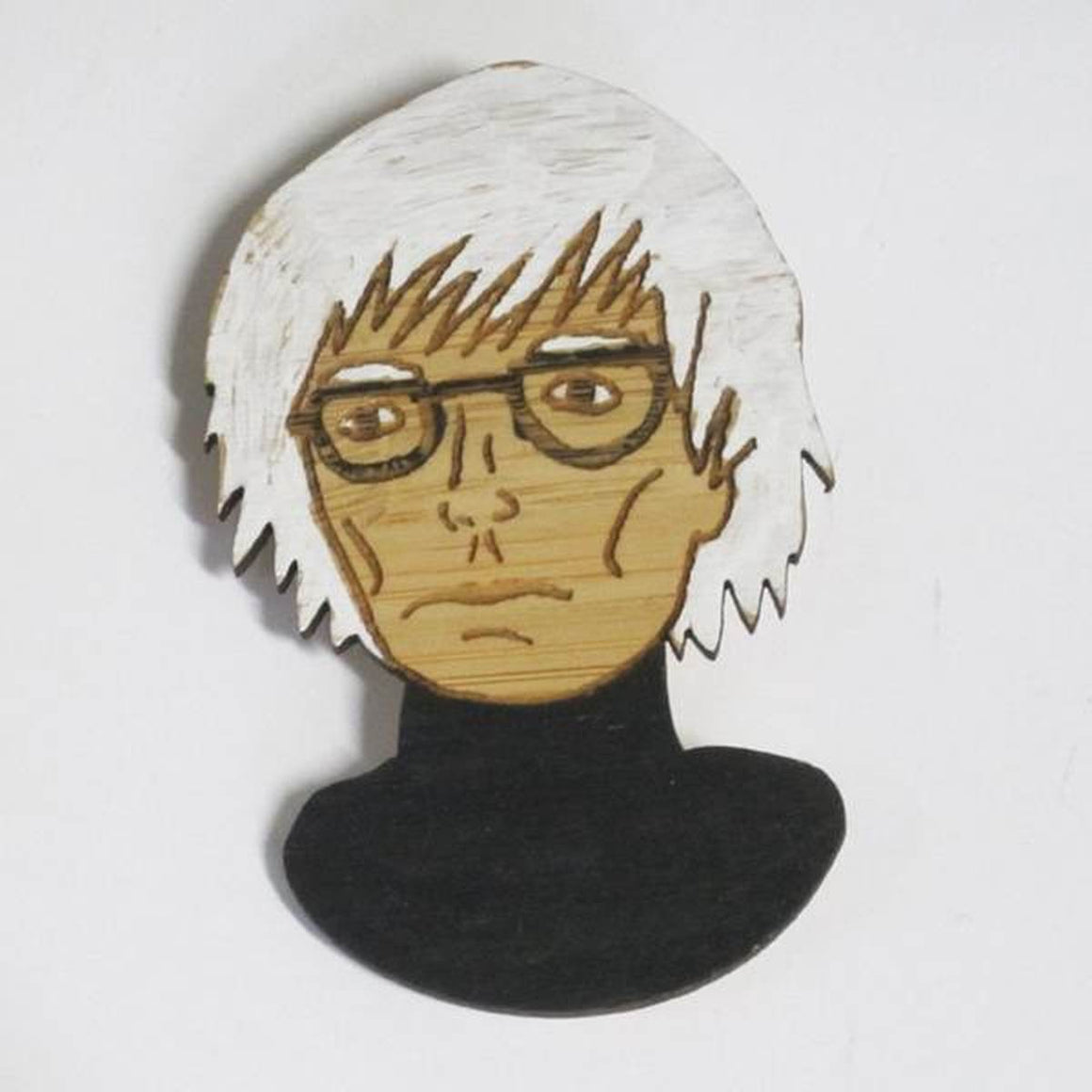 A brooch featuring a portrait of artist Andy Warhol. He is shown wearing a black turtleneck and his iconic glasses.Made from bamboo wood and hand painted.