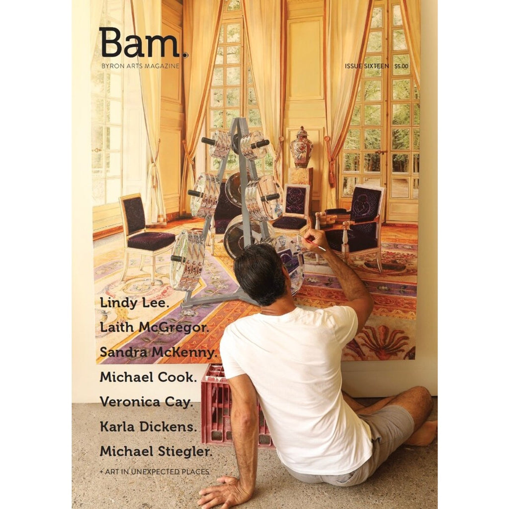 A magazine cover for Byron Arts Magazine. A Man sits on the floor applying paint to a Painting depicting a luxe indoor scene.