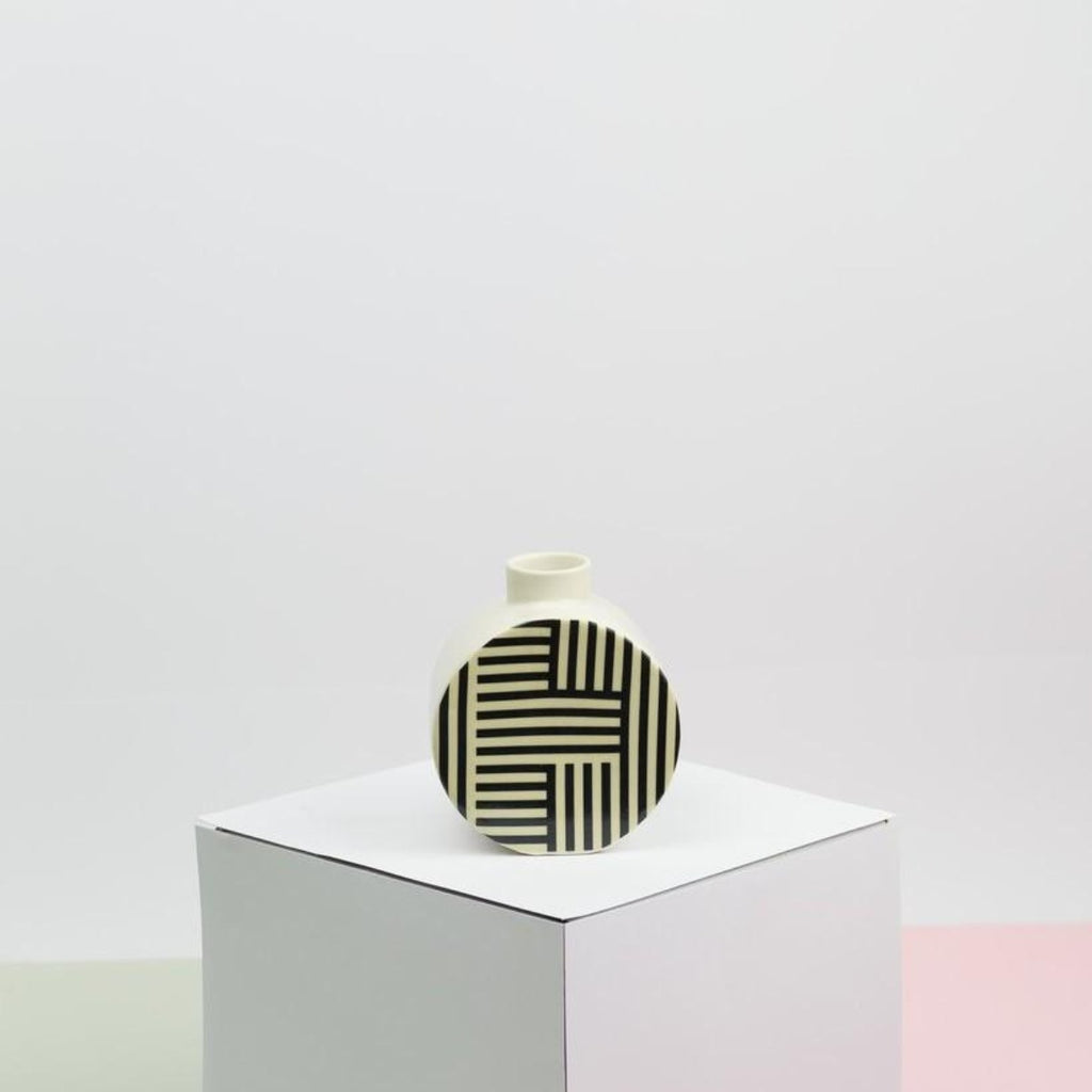 Image featuring a small ceramic vase in the centre of the image which features a decal on the front which includes vertical and horizonal black and white lines