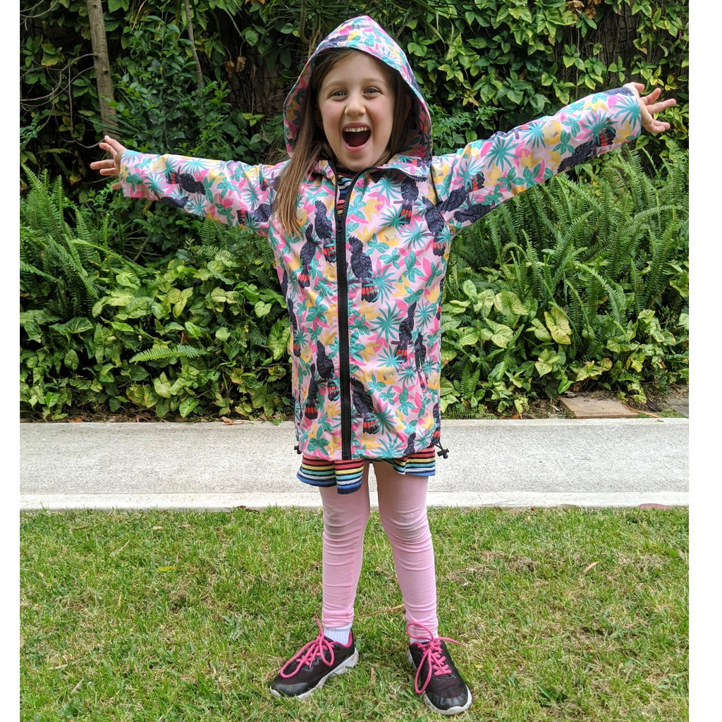 A Girl stands arms outstretched in the air in celebration. She wears a pink raincoat printed with a black cockatoo print.