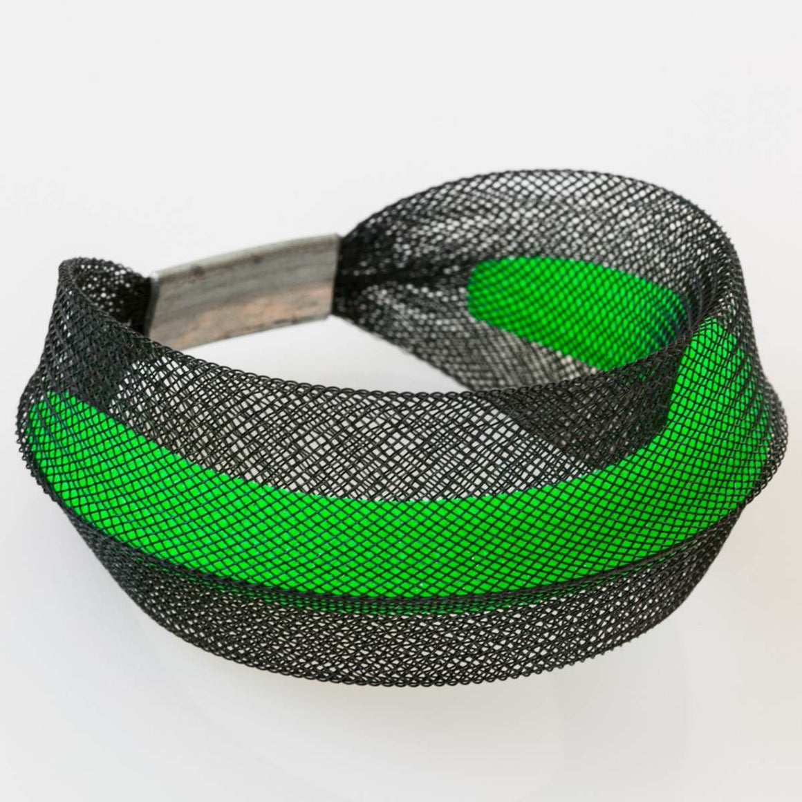 A Black and green bracelet made from finely woven nylon mesh. A Green Mesh tube is visible contained inside a black mesh tube.