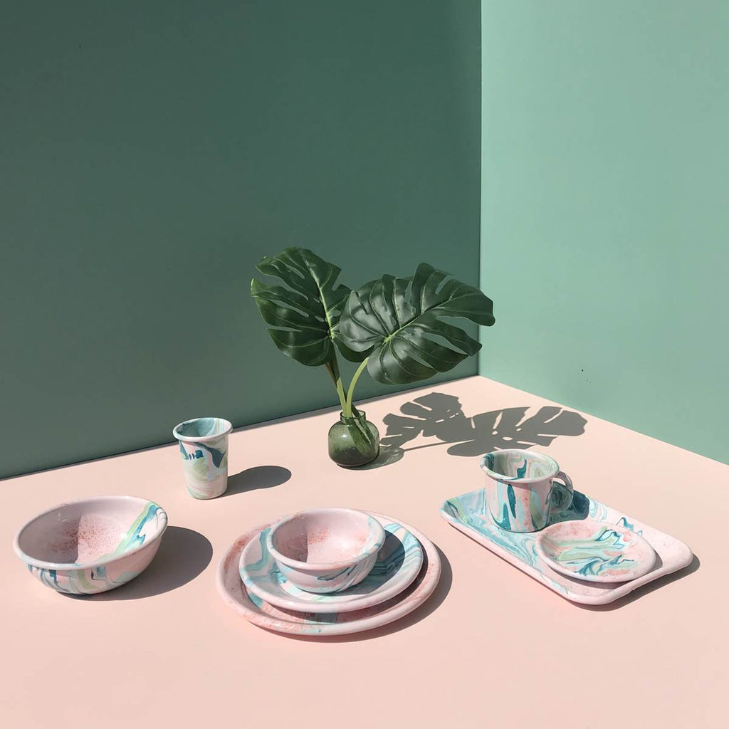 A pastel pink table, with an enamel dining set laid out. Beautiful marbled enamel in a range of contrasting tones of Turqouise and Green on a Blush Pink Base. The table is adorned with a vase of rainforest leaves