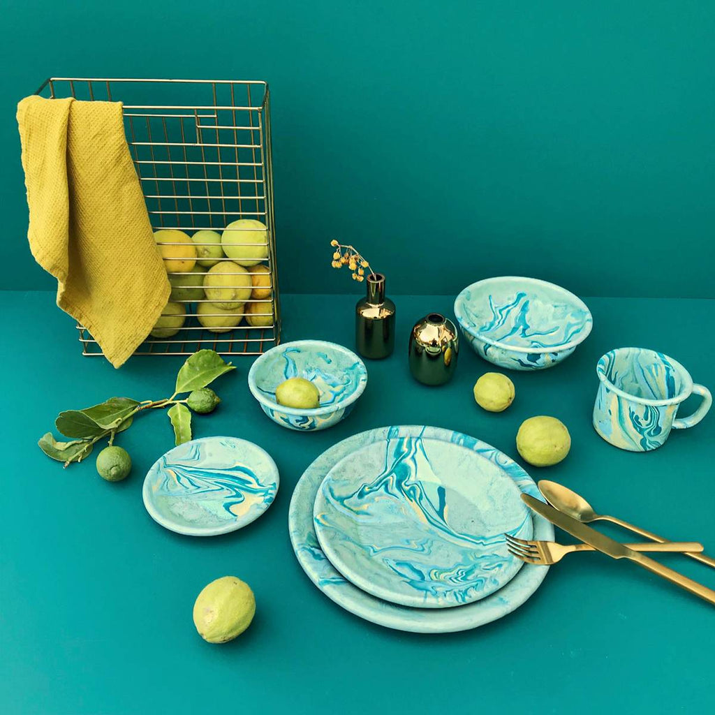 A range of enamel tablewear inclusing plates, bowls and mugs, on a turquoise background. Lemons, gold toned cutlery and a bright yellow tea towel are used as props