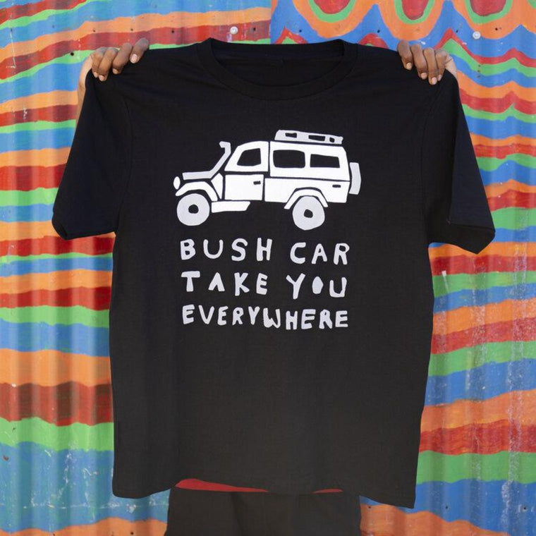 "A person displays a black tshirt, holding it up in front of them b the shoulders. An image of a 4WD and text in white features on the black t-shirt. The text reads ""Bush Car Take you everywhere"""