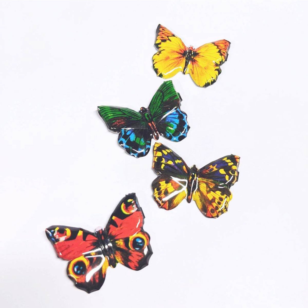 A group of four butterfly shaped tin brooches. They are in a range of colours: Red, Green, Yellow and Yellow/Purple