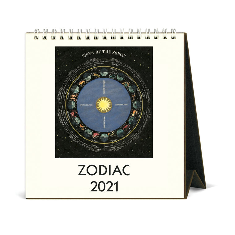 A small 2021 desk calendar, shown with easel stand open. The cover features a vintage zodiac image in bold colours.