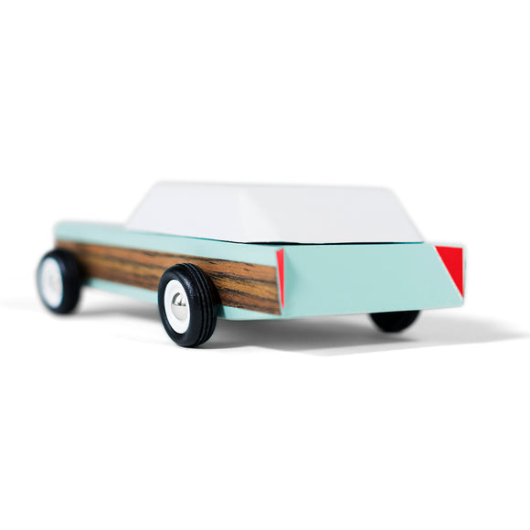 A pastel blue and white toy car in the style of a vintage American station wagon. Featuring a wood trim cladding along the side of the car.