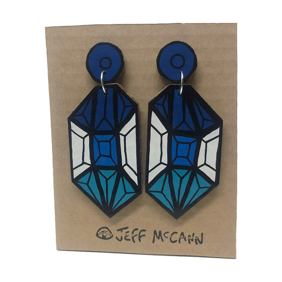 A Pair of Drop Earrings made of hand painted cardboard. A geometric design in the shape of a crystal, in blue tones and white.