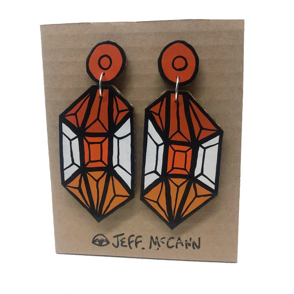 A Pair of Drop Earrings made of hand painted cardboard. A geometric design in the shape of a crystal, in orange tones and white.