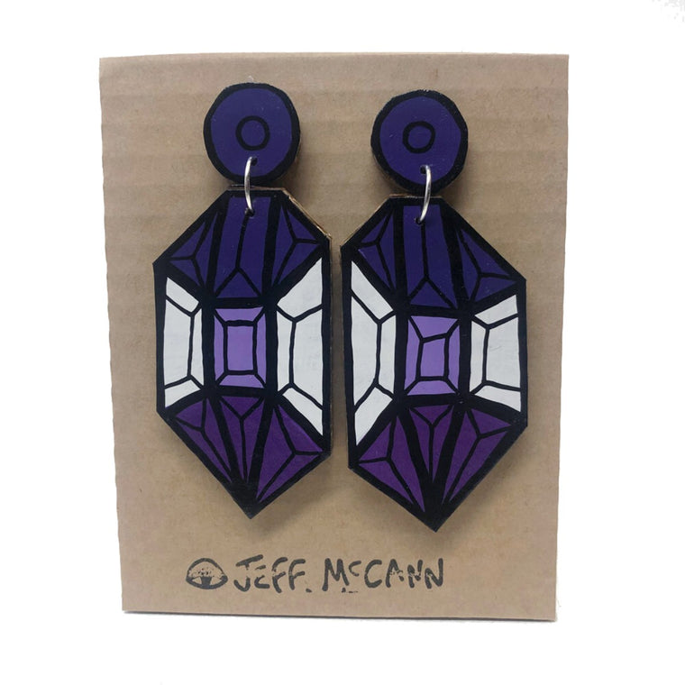 A Pair of Drop Earrings made of hand painted cardboard. A geometric design in the shape of a crystal, in purple tones and white.