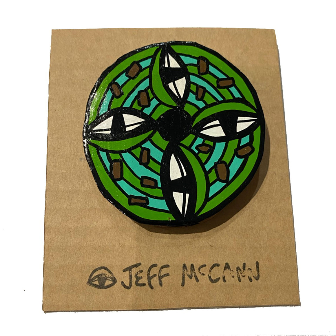 a Large Jeff McCann Brooch featuring  an green disc, eyes and cactus like shapes in green, teal and brown.