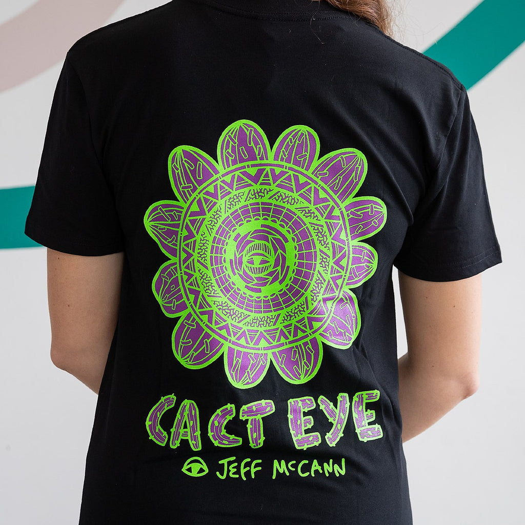 "A black T-Shirt featuring a bold circular Green and Purple work by Sydney artist Jeff McCann featuring eyes, cactuses, and bold abstract patterning. Text reads ""CACT EYE Jeff McCann"" in a Cactus inspired font. It is being modelled by a woman."