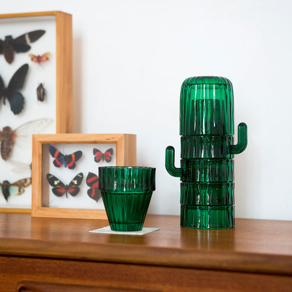 A set of green drinking glasses.  Featuring green ridged finish in order to imitate a Saguaro Cactus. Shown stacked one on top of the other, the stylised handles of the cups look like the branches of the cactus.