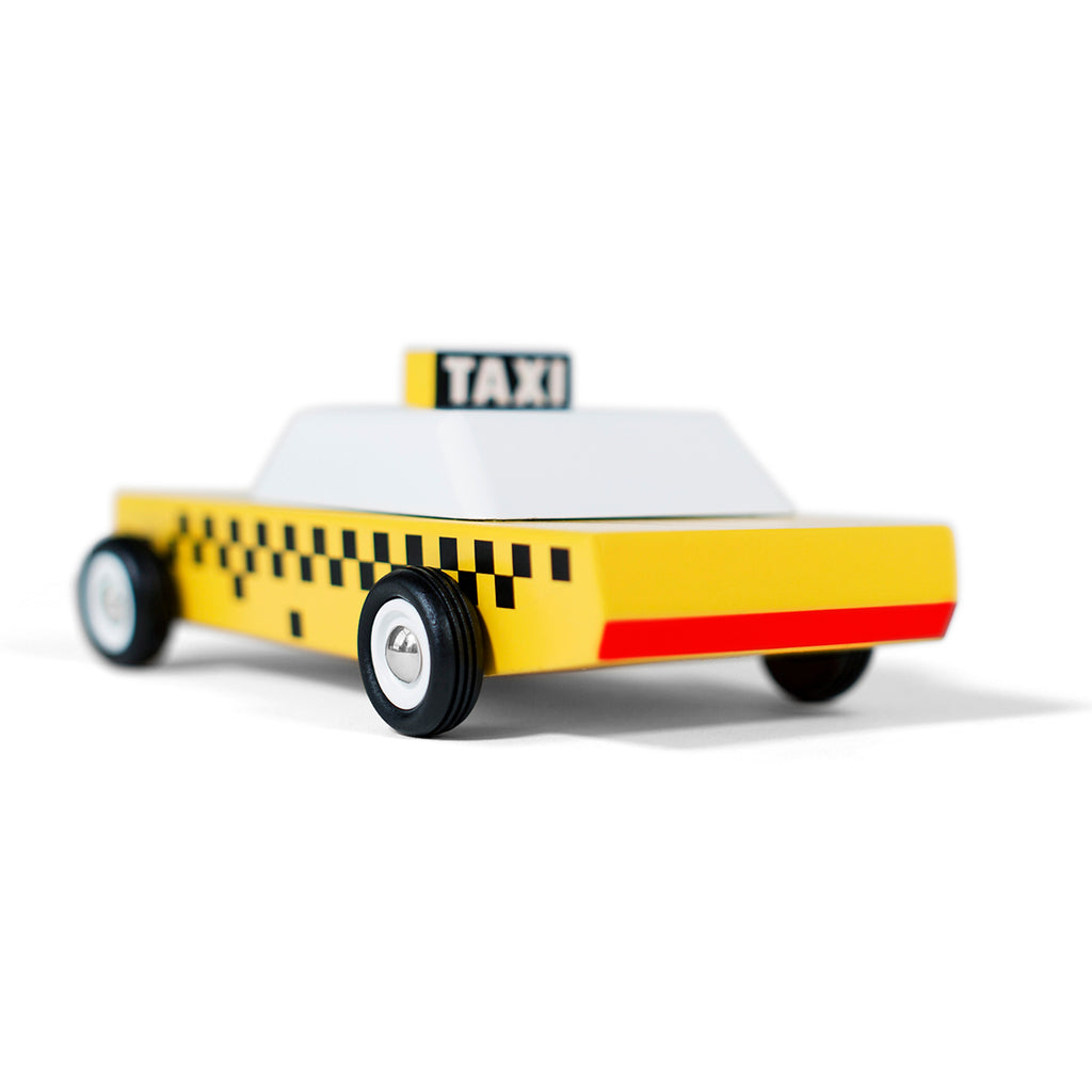 A Toy car in the style of an American taxi cab in yellow white and black. Red tail lights and a black and white taxi sign on the roof.